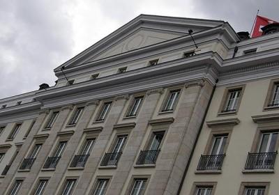 Façade d'un immeuble néo-classique surmontée d'un drapeau suisse à Genève les Bergues Four Seasons