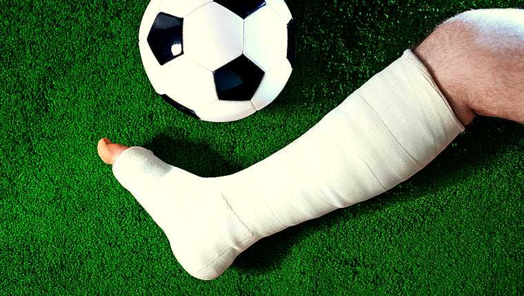 accident; ball; bandage; bone; broken; field; foot; football; fracture; grass; green; injury; lawn; leg; man; medical; medicine; one; people; plaster; player; profile; side view; soccer; sport; sportsman; vibrant; white;